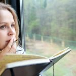 Woman staring out of a window while writing in a journal