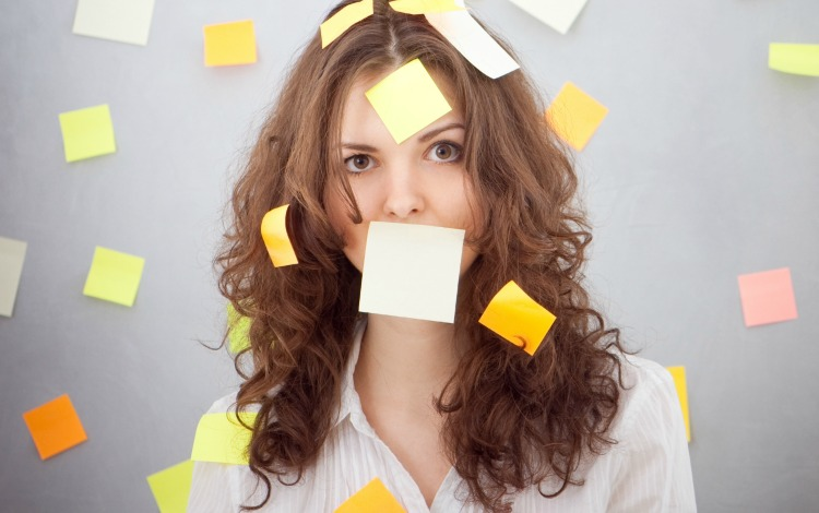 Woman with sticky notes all over, including over her mouth